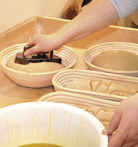 Die Brotlaibe werden vor dem Einschießen in den Holzbackofen mit dem Logo der Francke-Stiftung gestempelt.