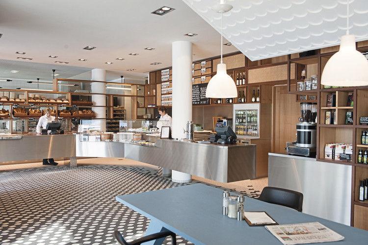 """Einladend und großzügig: Das Restaurant """"Das Brot."""" mit Brotregal. Dahinter schließt sich der Produktionsbereich an, der mit einer """"gläsernen Backstube"""" Kunden und Gästen Transparenz signalisieren soll."""