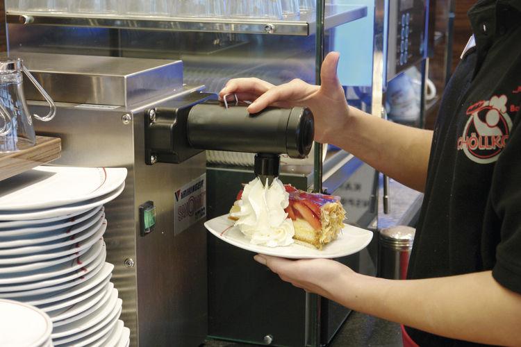 Die Sahne wird direkt am Kuchen portioniert.