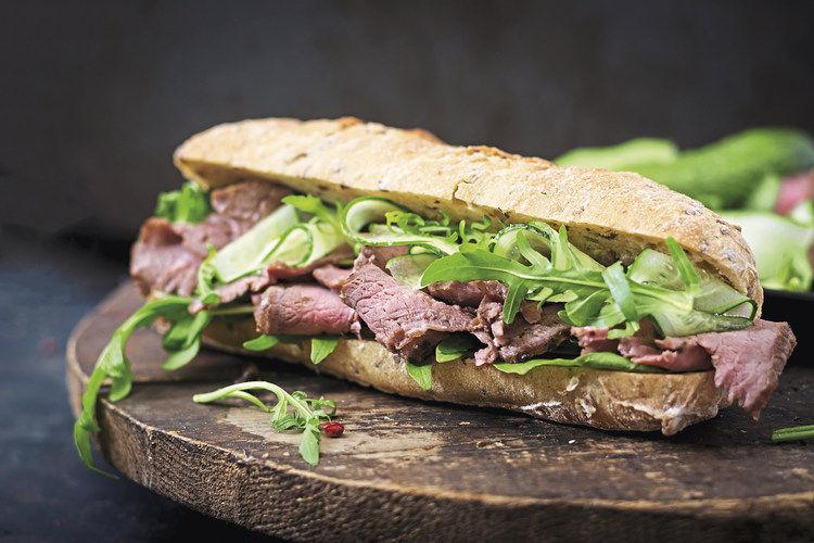 Pastrami-Sandwich als trendiger Snack: dünn aufgeschnittenes Rindfleisch auf Brot mit grüner Garnierung.