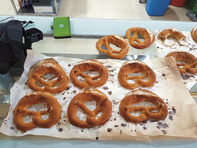 """Bäckermeister Michael Moll und seine """"Azubis"""" Alina und Cham mit einem Teil des Sortiments.  Links unten: Die Bäckerei – noch im Baustadium."""