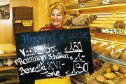 Die Verkäuferin Traudl Becker der Bäckerei Winzenhörlein mit den Werbeschild für die essbaren Papst-Souvenirs aus Marktl.