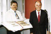 Emil Haußmann überreicht Prof. Dr. Leibinger eine Spezial-Torte.