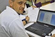 Karl Ernst Schmalz mit Laptop und Drucker zur Auswertung, für die Statistik und zum Ausdrucken der Ergebnisse und Urkunden.
