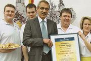 Verkaufsleiter Uwe Richter gratuliert Godehard und Doris Höweling (Mitte mit Urkunde) zum Gewinn des Heinrichsthaler Käsebrötchen-Awards.