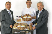"""Oberkirchenrat Dieter Kaufmann, Fachlehrer Joachim Burkart und Verbandsgeschäftsführer Andres Kofler (von links) stellten das """"Brot zum Teilen"""" vor."""