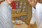 Bäckermeister Stefan Marks zeigt einem Schüler, wie man fachgerecht Zöpfe flechtet.