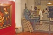 """Im Erdgeschoss begrüßt eine rekonstruierte Backstube von 1900 die Besucher des Museums. Daneben das Gemälde """"Arm und Reich oder Krieg und Frieden"""" eines Flämischen Meisters des 17. Jahrhunderts."""