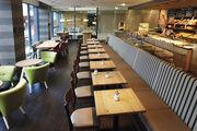 Klare Strukturen: Kleine Loungegruppen und lange Tische direkt am Fenster wirken einladend, die Rückenlehne der Bank trennt optisch den Thekenbereich.