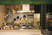 Pastaküche vom Bäcker: Mit Saucen können die Nudeln variiert werden. Augenmerk der Filiale ist aber der breite Tresen mit Brot, Brötchen und Kuchen. Alles gut ausgeleuchtet vor dunkelgrünem Hintergrund.