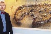 """Museumsdirektor Andrea Fadani posiert vor dem Bild """"Brot"""" von Dieter Krieg."""