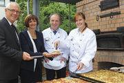 Wollte selbst schon mal eine Bäckerei gründen: Dr. Bettina Wolf (2. von links), hier mit dem ersten Stück der Holzofenpizza sowie Horst Müller, Leo Trumm und Landessiegerin Jennifer Bardt (von links).