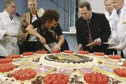 Gerlinde Kretschmann und Alexander Bonde (Mitte) schneiden die überdimensionale Torte an. Eberhard Holz (links) hatte die Idee.