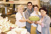 Hildegard Hummel, Andreas Ruckwied, Nadine Fink und Gabi Hofmann mit der Haustorte im neuen Backcafé der Bäckerei Hofmann. Heckenhaus, Kinderbereich, To-go-Station und das Frühstücksbüfett werden hier rege genutzt.