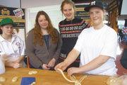 """Am Bäckerstand werben abwechselnd """"Azubinen"""" für einen Beruf im Bäckerhandwerk. Hier zeigt die angehende Bäckerin Stina Böttner (rechts) Schülerinnen, wie ein Hefezopf geflochten wird."""