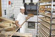 Bäckermeister und Müllergeselle: Josef Bauer an dem Holzbackofen, den sein Großvater 1928 bauen ließ. Mit zwei Walzenstühlen werden in der eigenen Mühle alle Mehle aus Bio-Getreide gemahlen.