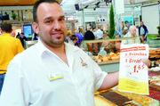 Bäckermeister und Ernährungsberater Jürgen Musler und seine Tochter Lizzy bieten Bio-Brot zum Verkosten an. Markus Nussbaumer verpackt Waren in Tüten, die einen günstigen Einkauf in einer Filiale ermöglichen.