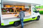 Alle 15 Frühstücksmobile von Dieter Hohlt (rechts) sind gleich aufgebaut, sie fahren im Umkreis von bis zu 130 Kilometer vom Firmensitz.