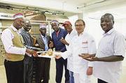 Pastor Idaki (links) und seine Kollegen freuen sich im Dezember 2014 über das erste frischgebackene Brot in der Angel Bakery.