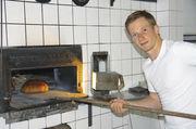 August Wieneroither junior demonstriert das Arbeiten an einem der alten Holzbacköfen, die noch zusätzlich zu den neuen Öfen genutzt werden. Täglich werden rund 500 Brote verkauft. Die Kilo-Laibe für 3,70 Euro. 2-Kilo-Laibe entsprechend teurer.