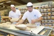 Sie bereiten die reifen Brotteiglinge zum Backen vor: Bäckermeister Gerd Mayer (rechts) und Carsten Denker.