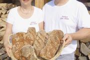 Petra und Björn Pfeifer mit Broten aus dem Holzbackofen.