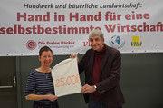 Symbolische Übergabe: Anke Kähler, Vorstandsvorsitzende der Freien Bäcker, überreicht Oliver Willing, Geschäftsführer vom Saatgutfonds Zukunftsstiftung Landwirtschaft, den Spendenerlös.