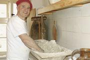 Hartmut Priemer knetet von Hand den Brotteig in der altertümlichen Teigwanne.