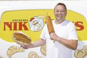 Jürgen Nikolaus – Bäckermeister aus Waldrennach mit seinem Holzofenbrot vor dem Firmenlogo.