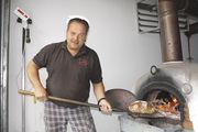 """Teamwork: Miguel Szczes backt die Brote im Holzofen, die Verena Gangel als """"Einzugsbrote"""" einpackt."""