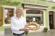 Aushängeschild: Jutta Striffler mit einer der Brezeln, wie sie auch im Schaufenster der Bäckerei hängen.