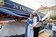 Das Stollenmädchen Hanna Haubold und Bäckermeister René Krause schneiden medienwirksam den Riesenstollen an.