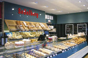 Thekenvielfalt: Brotsorten, Brötchen, Croissants, große Kuchenvielfalt bis zu warmen Gerichten.