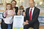 """Geschäftsführerin Heike Brinkhege hält mit Kindern die Urkunde für eine """"Familienfreundliche Gastronomie""""."""