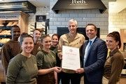 Dirk Strangfeld, Leiter der Agentur für Arbeit Krefeld, überreicht Heinrich Poeth in seinem Café das Ausbildungs-Zertifikat - da strahlen auch die Poeth-Azubis.