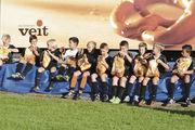 So geht erfolgreiche Werbung: junge Kicker in Trikots, vor Werbewand und mit Produkt des Sponsors.
