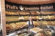 Die Hand am Brot: Verkäuferin vor dem Motto der Bäckerei Pfaff.