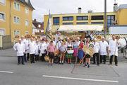 Mitglieder des Straubinger Fachvereins der Bäcker und Konditoren mit Fahne und geschmücktem Festwagen bei der Aufstellung vor dem Festzug zur Eröffnung des Gäubodenvolksfests in Straubing.