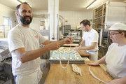 Mit Spaß bei der Sache: Bernd Dannenmann (links) und seine Mitarbeiter beim Brezelschlingen in der Backstube.