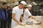 Chinesische Besucher beobachten das Arbeiten der Bäcker.