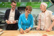Annegret Kramp-Karrenbauer versucht sich im Brezelschlingen, unterstützt von Daniel Schneider und Tanja Angstenberger.
