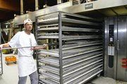 """Bäckermeister Jörg Weigel zeigt, wie das Roggenbrot """"Oppa Ewald"""" vom Beschickungswagen direkt auf den Herdwagen übertragen wird."""