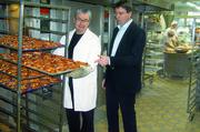 Bayerns Landesinnungsmeister Heinz Hoffmann (links) demonstriert Florian von Brunn (Verbraucherpolitischer Sprecher der SPD-Fraktion im Bayerischen Landtag) die Verfahren zum Abbacken belaugter Brezelteiglinge.