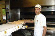 Michael Schwarzmaier beim Beschicken des vollautomatischen Pellets-Etagenofen von Mondial Fosni mit französischen Baguettes.