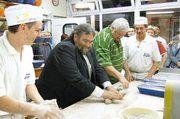 Übung macht den Meister: Unter dem wohlwollenden Blick von Bäckermeister Friedbert Englert (r.) unternahmen MdEP Dr. Thomas Ulmer (2.v.l.) und Fleischermeister Dieter Mehl (2.v.r.) den ambitionierten Versuch, Brot so zu formen, dass es auch in eine B