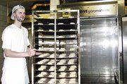 Schichtleiter Michael Lange füllt den Gärvollautomaten mit Brötchenteiglingen für den nächsten Morgen.