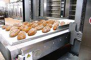 Ausbackvorgang mit dem Ober. Nach dem das Brot aus dem Ofen entnommen ist, wird es automatisch nach hinten auf ein Transportband befördert.