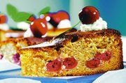 """Sauerkirschkuchen mit Sahnegarnitur.  Das Foto ist entnommen aus dem Kalender """"Sonntagskuchen 2006"""" des Stadler Kalenderverlags."""