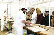 Bäckermeister Kuttenreich (M.) war immer wieder vollauf damit beschäftigt, den Besuchern, die sich vor der gläsernen Backstube versammelten, die Produktionsvorgänge hinter der Glasscheibe zu erklären.