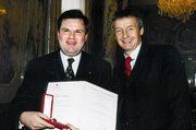"""Bundesminister Dr. Bartenstein (rechts) gratuliert Dr. Reinhard Kainz (links) zur Verleihung des """"Silbernen Ehrenzeichen""""."""